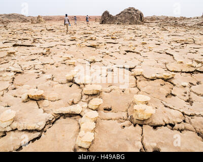 People walk across mineral soil formations around sulfur lake Dallol, Danakil Depression, Ethiopia, the hottest - Stock Photo