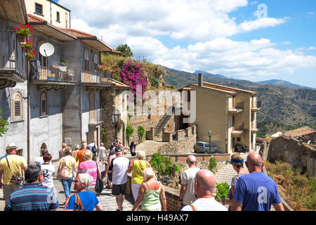 A tourist group on a visit to the mountain village of Savoca on the island of Sicily, Italy. - Stock Photo