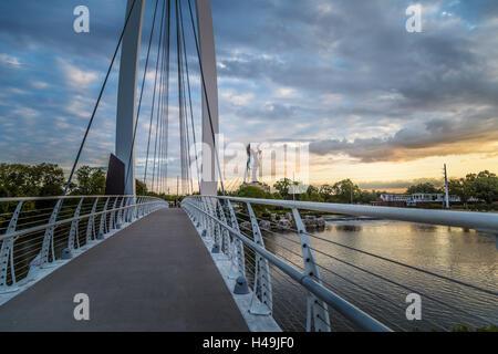 Keeper of the Plains in Wichita, Kansas bridge near sunrise - Stock Photo