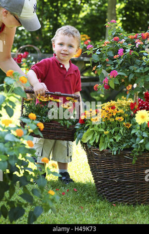Small child, boy with basket of flowers in the garden, sunhat, Spanish flag, Gazanie, Spanish flag, Dahlia, Rudbeckia, - Stock Photo