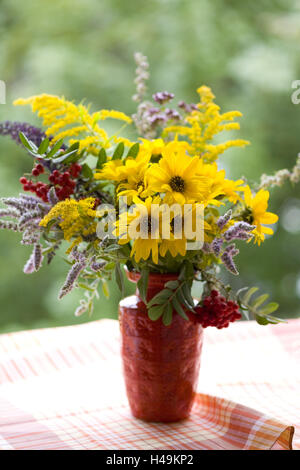 Bouquet in red vase on checked cloth, - Stock Photo