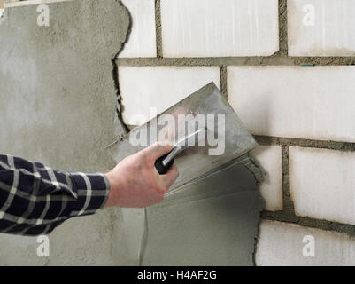 Building site, shell construction, man, hand, wall, plaster - Stock Photo
