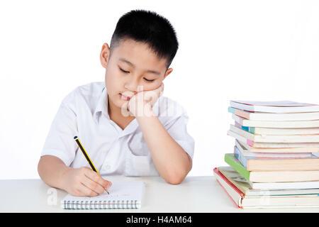 Bored Asian Chinese Little Boy Wearing Student Uniform Writting Homework in plain isolated white background. - Stock Photo