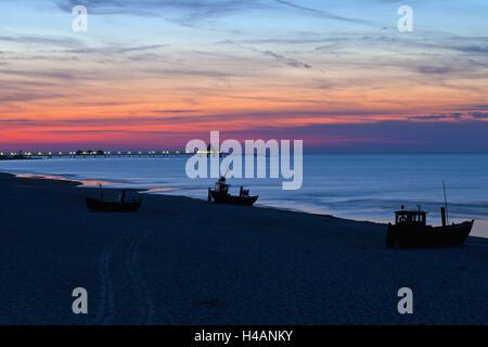 Germany, Western Pomerania, island Usedom, seaside resort Ahlbeck, beach, fishing boats, pier Heringsdorf, dusk, - Stock Photo