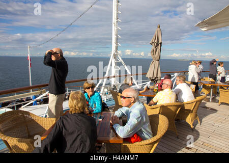 Passengers gather on the aft deck of Windstar Cruises' sail-cruiser Wind Surf as the vessel sails from Copenhagen, - Stock Photo