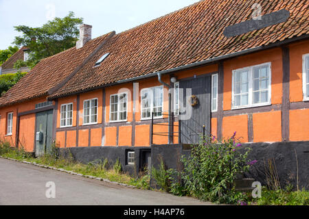 Colorful tiled roof shops and houses characterize the coastal village of Svaneke on the Danish island of Bornholm. - Stock Photo