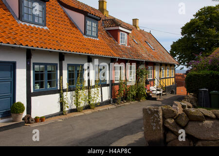 Colorful tiled-roof shops and houses characterize the coastal village of Svaneke on the Danish island of Bornholm. - Stock Photo