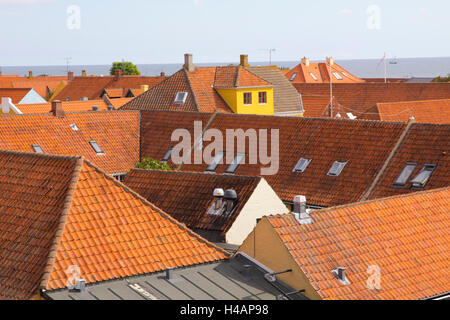 Colorful tiled-roof houses and shops characterize the coastal village of Svaneke on the Danish island of Bornholm. - Stock Photo