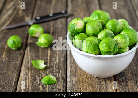 fresh Brussels sprouts in white on wooden table - Stock Photo