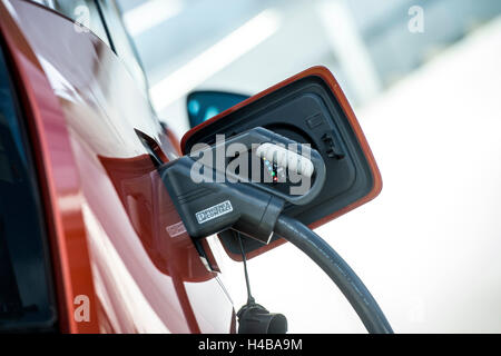Electric car is being charged at a charging station - Stock Photo