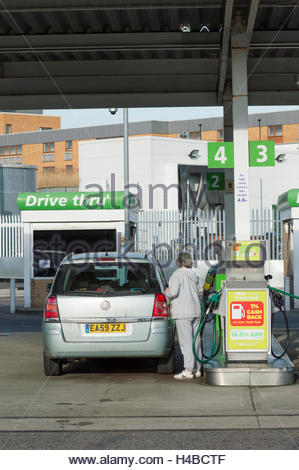 Woman finishing filling her car at ASDA Petrol station, Greenhithe, Kent, England UK - Stock Photo