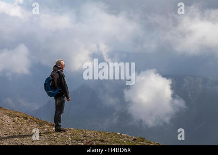 A hiker looking over mountaintop - Stock Photo