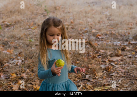 Little girl holding a small pumpkin in her hand - Stock Photo