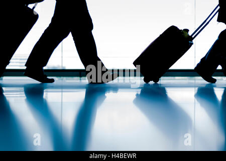 Silhouette group of passenger walking with luggage at airport - Stock Photo