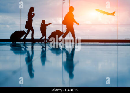 Silhouette of young family and airplane at airport - Stock Photo