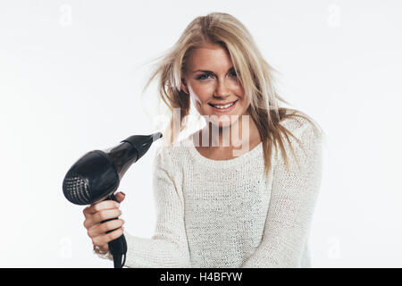 Woman blow-drying her hair - Stock Photo