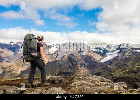 A young hiker overlooking a glacier in Thorsmörk - Stock Photo