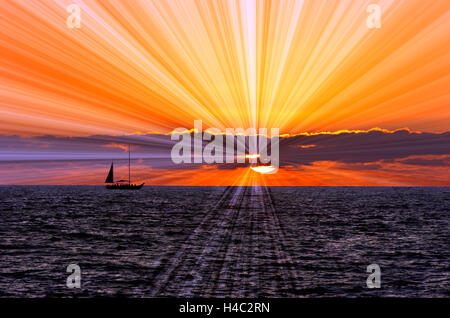 Sunset sailboat is a silhouetted boat sailing along the ocean water withe a sun burst of rays flowing out from the - Stock Photo