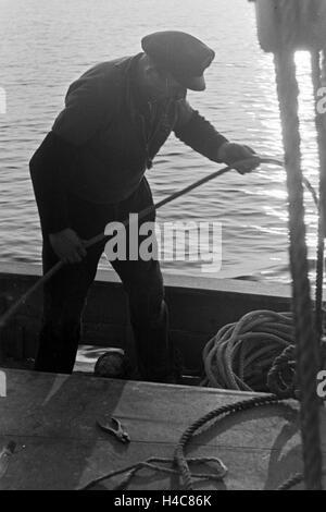 Ein Hochseefischer bei der Arbeit an Deck, Deutschland 1930er Jahre. A deep sea fisherman working on deck, Germany - Stock Photo