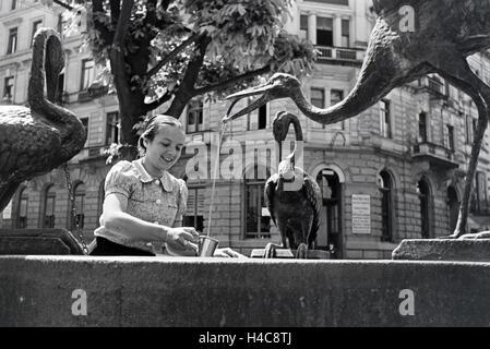 Eine junge Frau probiert das warme Thermalwasser aus dem Reiherbrunnen in der Sophienstraße der Innenstadt von Baden - Stock Photo
