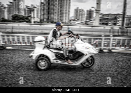 Older man on an electric scooter - Stock Photo