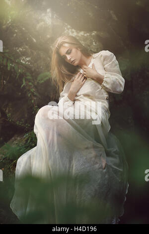 Graceful woman posing in dreamy forest. Ethereal and fantasy - Stock Photo