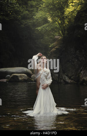 Beautiful woman posing in dreamy mountain stream. Fantasy and surreal - Stock Photo