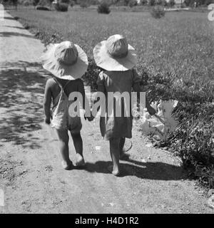 Zwei kleine Kinder bei einem Spaziergang in der Sonne, Deutschland 1930er Jahre. Two toddlers strolling through - Stock Photo