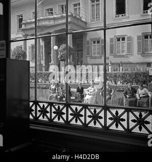 Blick aus dem Fenster eines Weinlokals in Wildbad im Schwarzwald auf Menschen, die auf Bänken eine Pause machen, - Stock Photo