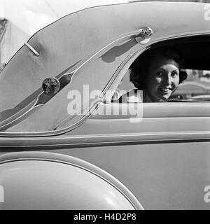Eine junge Frau schaut aus dem Fenster eines abgedeckten Cabrio Ford V8, Deutschland 1930er Jahre. A young female - Stock Photo