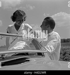 Ein junger Mann und eine junge Frau an einem Ford V8 Cabrio, Deutschland 1930er Jahre. A young man and a young woman - Stock Photo