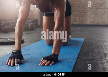 Female on exercise mat doing stretching workout. Focus on hand of a woman on fitness mat. - Stock Photo
