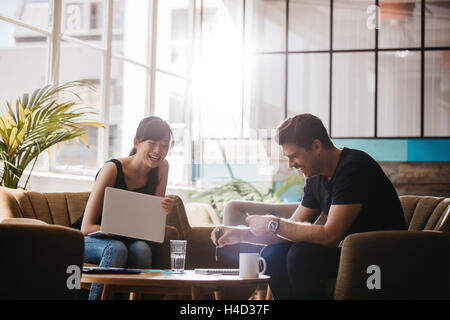 Two businesspeople having meeting in cafe. Smiling business colleagues working together in office lobby. - Stock Photo