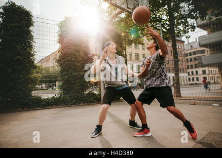 Teenage friends playing basketball against each other on an outdoor court. Two young men playing a game of basketball. - Stock Photo