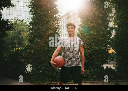 Portrait of young man holding a basketball on outdoor court. Smiling teenage streetball player looking at camera. - Stock Photo