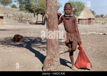 Portrait of himba girl into the village near Opuwo town in Namibia, South Africa - Stock Photo