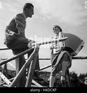 Ein junger Mann und eine Frau mit einem Akkordeon, Deutschland 1930er Jahre. A young man and a woman with an accordion, - Stock Photo