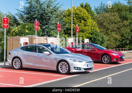 Tesla model s electric cars at recharging point, Hopwood Service Station Birmingham UK GB EU Europe - Stock Photo