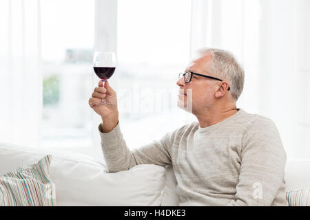 senior man drinking red wine from glass at home - Stock Photo