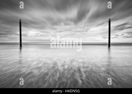 Navigation guide posts in the North Sea off the Northumberland coast on an overcast day, long exposure creative effect Stock Photo