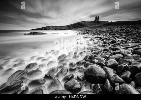 The ruins of Dunstanburgh Castle at Embleton Bay in Northumberland, long exposure from the boulder field rocky shore - Stock Photo