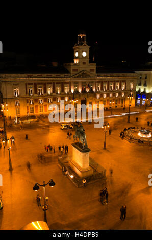 Puerta del Sol, people mill around the plaza at night. - Stock Photo