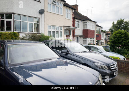 Cars parked on the front drive of houses in Barnet, North London, England, UK - Stock Photo