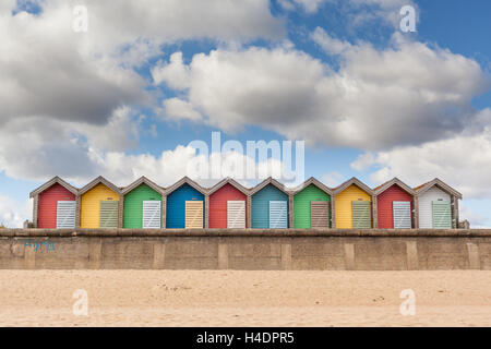 A row of multi-coloured beach huts on a summer's day by the beach, every colour of the rainbow at Blyth, Northumberland - Stock Photo