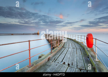 Blyth pier on the Northumberland coast at Blyth Harbour, an old wooden curving pier with a bright orange lifesaver ring
