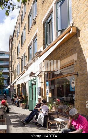 People sitting outside cafes in Ashwin Street, Dalston, Hackney, London, England, UK - Stock Photo
