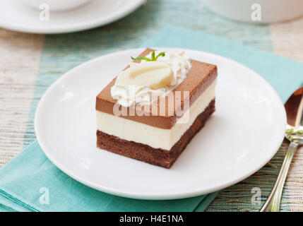 Three chocolate mousse cake on a white plate - Stock Photo