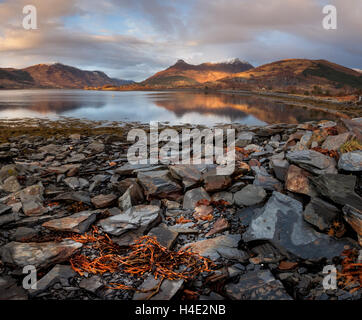 The Pap of Glencoe and surrounding mountains on the slate shores of Loch Leven in the Scottish Highlands in winter - Stock Photo