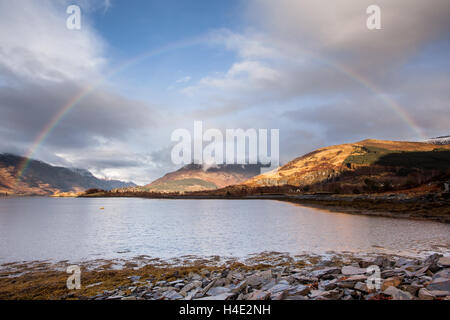 Rainbow over the Pap of Glencoe on the shores of Loch Leven in the Scottish Highlands in winter time - Stock Photo