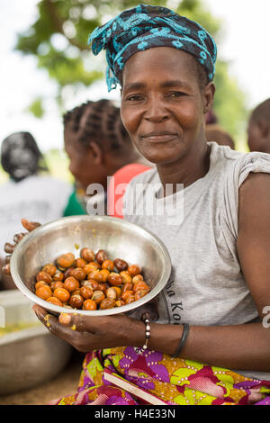 A woman holds a bowl of freshly harvested shea nuts in in rural Réo Department, Burkina Faso. - Stock Photo